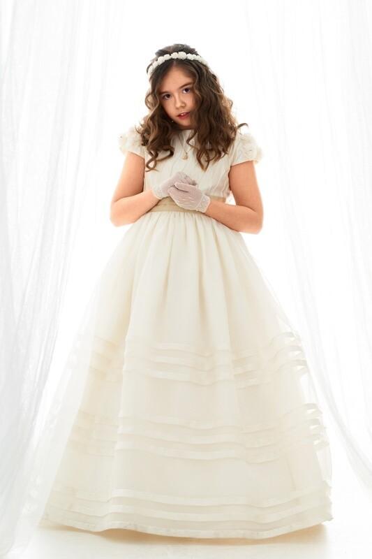 niña vestida de comunión entre cortinas blancas