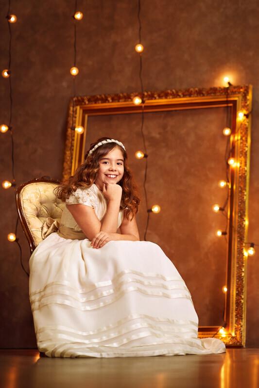 niña sentada en trono con marco dorado