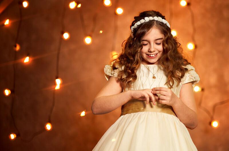 niña ajustándo el anillo que le han regalado por su comunión