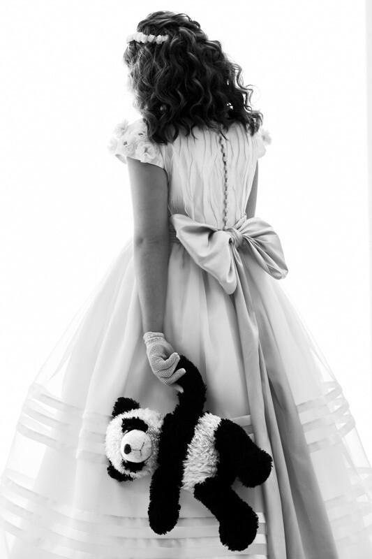 niña con vestido de comunión y osito de peluche